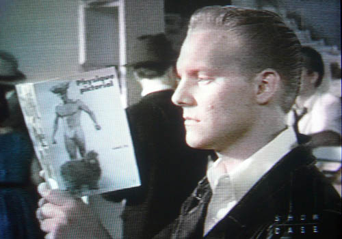 Jonathan Torrens in a leather jacket reading 'Physique Pictorial'