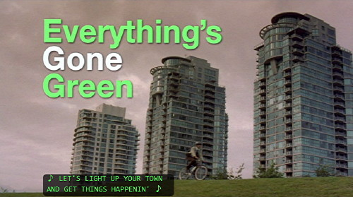 Screenshot shows 'Everything's Gone Green' title in green and white Helvetica type, with Vancouver see-throughs in the background, a bicyclist, and a caption
