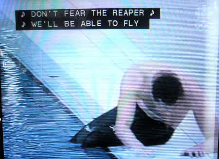 Swimmer barely holds himself up by the edge of a pool. Caption: ♪ DON'T FEAR THE REAPER ♪