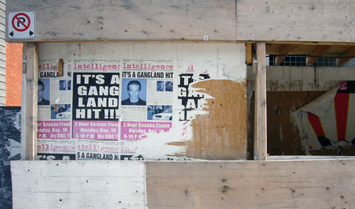 Decaying posters on construction hoarding read Intelligence IT'S A GANGLAND HIT!