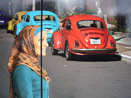 Close-up of photo of Rayyan from 'Little Mosque' crossing a street where three old Beetles are parked