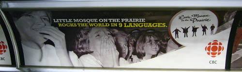 Subway ad shows thrilled teenage girls (as at a Beatles concert) and the headline LITTLE MOSQUE ON THE PRAIRIE ROCKS THE WORLD IN 9 LANGUAGES