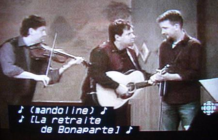 Fiddler, guitarist, and mandolinist play, with captions reading ♪ (mandoline) ♪  ♪ [La retraite de Bonaparte] ♪