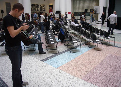 Young photographer inspects camera as he stands alongside a sea of mostly-unfilled chairs