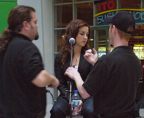 Two guys in black T-shirts seem to tend to Erin as she turns to the side with eyes closed