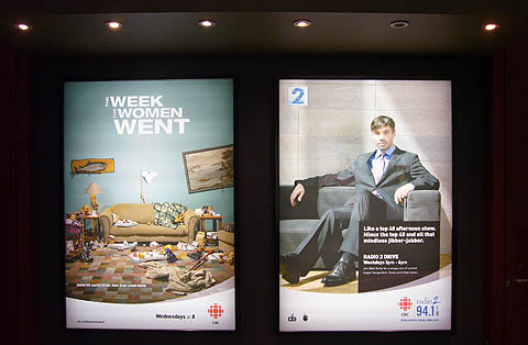 Two billboards in illuminated caissons: One for 'The Week the Women Went,' another showing Rich Terfry for Radio 2