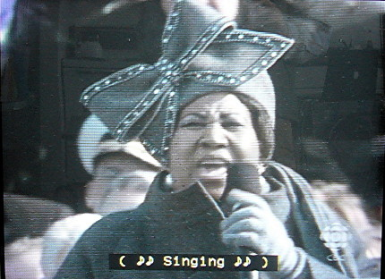 Aretha Franklin wears a grey outfit with matching hat and huge bow. Caption reads ( ♪♪ Singing ♪♪ )