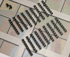 Diagonal ranks of empty black chairs seen from overhead