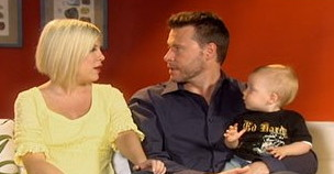 Blond Tori Spelling looks at her husband, Dean Whatever, as he holds a baby