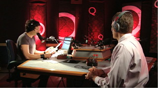 Ghomeshi interviews guest in radio studio with glowing red 'Q' backdrops