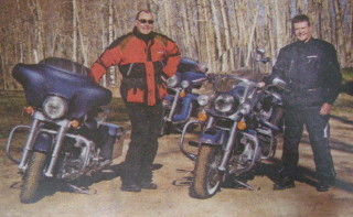Jeff Keay leans against blue Harley with a friend nearby