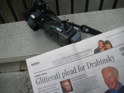 'Toronto Star' headline reads 'Glitterati plead for Drabinski' as video camera and CBC mike sit nearby
