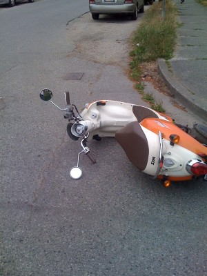 Scooter laying on its side on street by curb