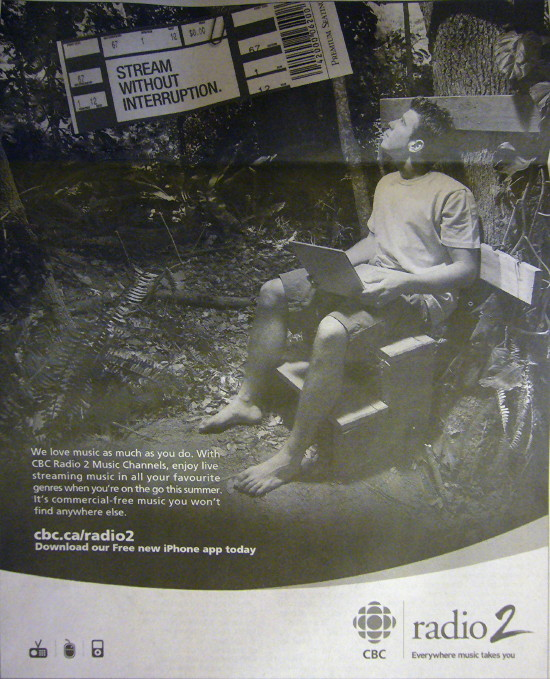 Shoeless young man in T-shirt and shorts sits with laptop in dense forest