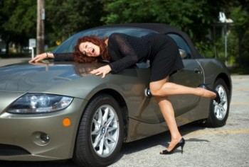 Lynne Russell sprawled on the hood of her BMW Z4