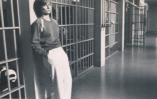 Young woman in sweatshirt and white trousers leans against cellblock doors in prison hallway