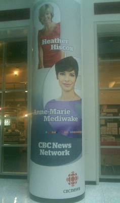 Poster on column of building advertising CBC News Network and two news anchors